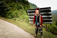Vietnam, Sapa. Red Dzao woman carrying a corrugated iron on her back.