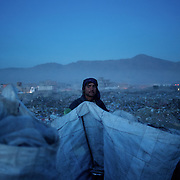 November 14, 2012 - Kabul, Afghanistan: An Afghan Pashtun boy, who said he was forced from the troubled province of Baglan due to threats from the Taliban, scavenges for recyclables at a garbage dump site in Kabul. (Paulo Nunes dos Santos)