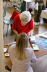 Age concern carers week; lady chatting at the NHS stall,