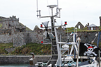 Boat with pirate flag in front of Peel Castle, Isle of Man. Peel castle is one of Isle of Man's principal historic monuments, situated on the St Patrick's Isle at Peel. Build in 11th century