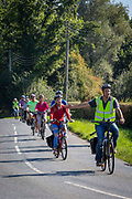 A male tour guide indicates the cycling group needs to turn right on a country road in Staplehurst, Kent, England, UK.
