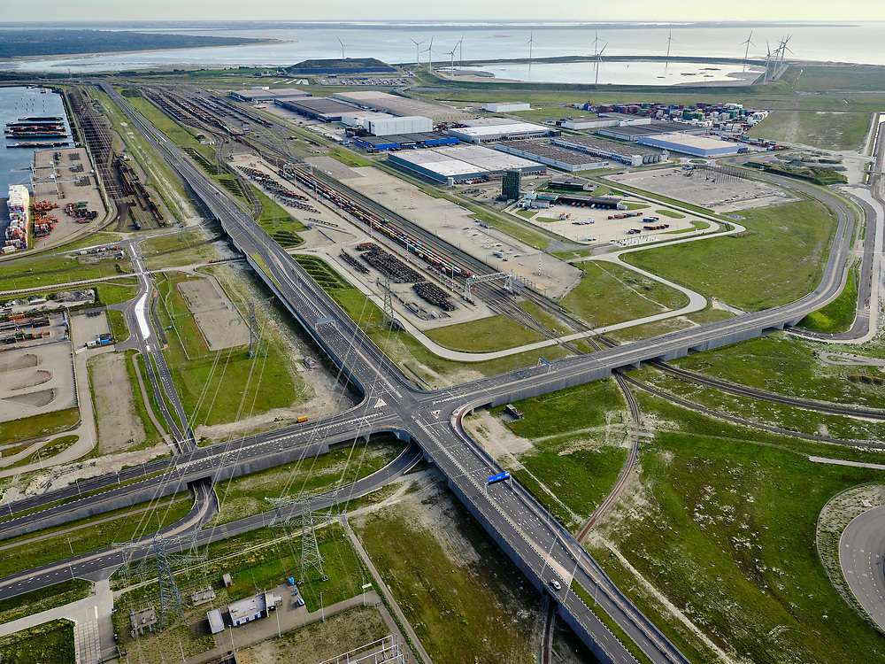 Nederland, Zuid-Holland, Rotterdam, 14-09-2019; Maasvlakte 2 ofwel Tweede Maasvlakte, MV2. Kruising Europaweg N15 met Dardanellenstraat / Coloradoweg. Logistieke dienstverlening en overslag en rangeerterrein / spoorterminal Betuweroute. De SLufter, baggerdepot, in de achtergrond.<br /> Maasvlakte 2 or Second Maasvlakte, MV2. Crossing Europaweg N15 with Dardanellenstraat / Coloradoweg. Logistic services and transshipments rail terminal Betuwe route.<br /> luchtfoto (toeslag op standard tarieven);<br /> aerial photo (additional fee required);<br /> copyright foto/photo Siebe Swart