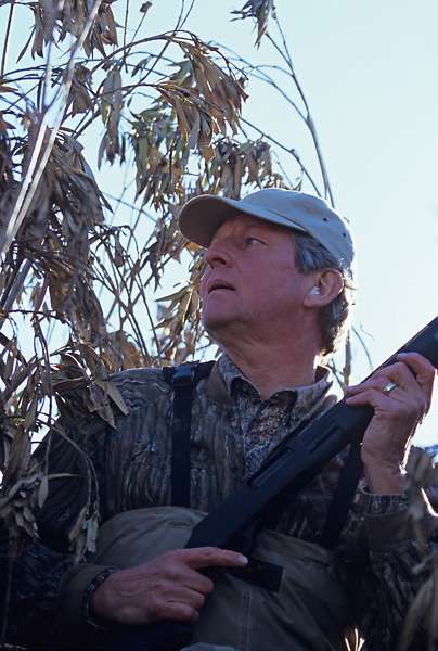 Stock photo of an older man holding a shotgun waiting for ducks to fly by