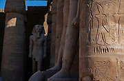 Rameses II statue with column and hieroglyphics in the foreground, Karnak Temple, Luxor