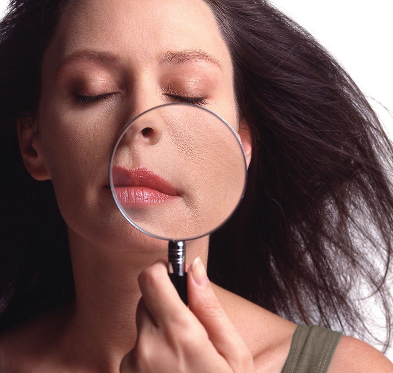 Woman holding magnifying glass in front of face showing a close up of skin and pores. Windswept hair.