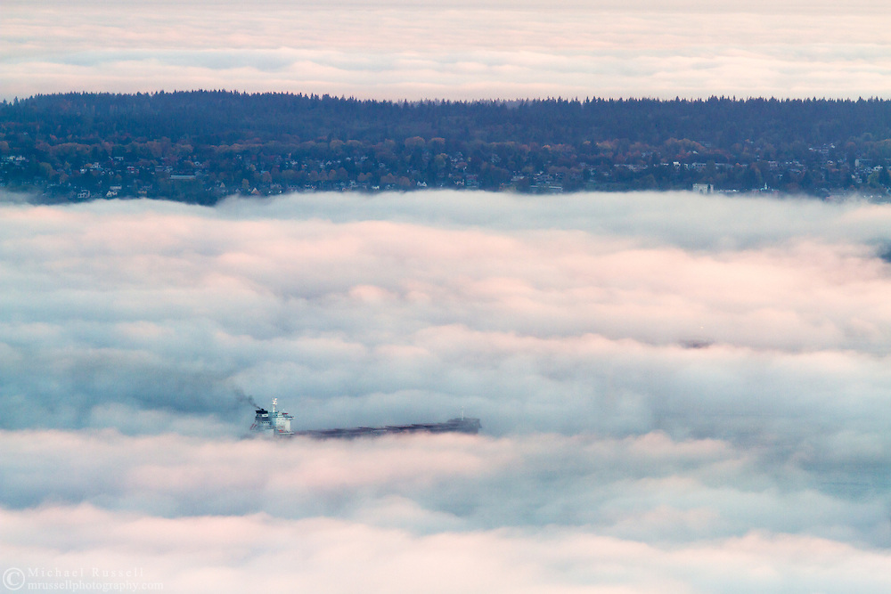 A Freighter anchored in English Bay surrounded by fog with Point Grey in the distance.  Photographed from the Cypress Lookout in Cypress Provincial Park in West Vancouver, British Columbia, Canada.