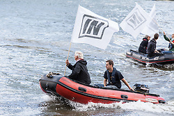 © Licensed to London News Pictures. 15/06/2016. London, UK. A rib boat flying an 'IN' flag meets a flotilla of pro-Brexit fishing trawlers, led by UKIP leader Nigel Farage, as they sail up the River Thames to Westminster. The flotilla is organised by the 'Fishing for Leave' campaign, founded by Scottish fisherman, which argues that the UK's fishing industry would be better off outside the EU, but with the same status as Iceland or Norway when fishing quotas are negotiated. Photo credit: Rob Pinney/LNP