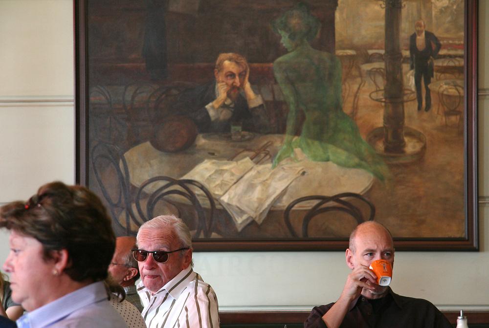 "G‰ste im ber¸hmten Kaffeehaus SLAVIA in der Prager Innenstadt. Im Hintergrund das Gem‰lde ""Der Absinthtrinker"" von Maler Viktor Oliva.<br /> <br /> Visitors at the famous CafÈ Slavia in the city centre of Prague. In the back a painting by Viktor Oliva with the title the Absinth drinker."