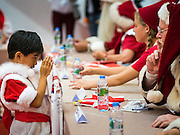 """17 SEPTEMBER 2015 - BANGKOK, THAILAND: A Thai boy dressed as a Christmas elf, """"wais"""" a Santa Claus at the World Santa Claus Congress. The """"wai"""" is the traditional Thai greeting. Twenty-six Santa Clauses from around the world are in Bangkok for the first World Santa Claus Congress. The World Santa Claus Congress has been an annual event in Denmark since 1957. This year's event, hosted by Snow Town, a theme park with a winter and snow theme, hosted the event. There were Santas from Japan, Hong Kong, the US, Canada, Germany, France and Denmark. They presented gifts to Thai children and judged a Santa pageant. Thailand, a Buddhist country, does not celebrate the religious aspects of Christmas, but Thais do celebrate the commercial aspects of the holiday.    PHOTO BY JACK KURTZ"""