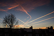 Contrail clouds from passing jet planes streak the sky over London. ontrails are clouds formed when water vapor condenses and freezes around small particles (aerosols) that exist in aircraft exhaust. Some of that water vapor comes from the air around the plane; and, some is added by the exhaust of the aircraft. The exhaust of an aircraft contains both gas (vapor) and solid particles.