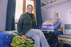 Young woman sitting on bed in bedsit at direct access hostel for homeless and vulnerably housed young people,