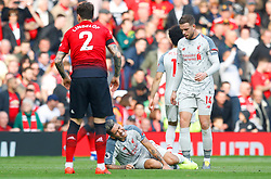 Liverpool's Roberto Firmino (bottom centre) goes down after picking up an injury during the Premier League match at Old Trafford, Manchester.