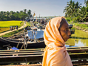 09 NOVEMBER 2014 - SITTWE, RAKHINE, MYANMAR: A Rohingya Muslim woman crosses a bridge into a Rohingya Muslim IDP camp near Sittwe. After sectarian violence devastated Rohingya communities and left hundreds of Rohingya dead in 2012, the government of Myanmar forced more than 140,000 Rohingya Muslims who used to live in and around Sittwe, Myanmar, into squalid Internal Displaced Persons camps. The government says the Rohingya are not Burmese citizens, that they are illegal immigrants from Bangladesh. The Bangladesh government says the Rohingya are Burmese and the Rohingya insist that they have lived in Burma for generations. The camps are about 20 minutes from Sittwe but the Rohingya who live in the camps are not allowed to leave without government permission. They are not allowed to work outside the camps, they are not allowed to go to Sittwe to use the hospital, go to school or do business. The camps have no electricity. Water is delivered through community wells. There are small schools funded by NOGs in the camps and a few private clinics but medical care is costly and not reliable.  PHOTO BY JACK KURTZ