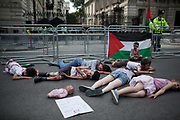 Children play dead outside Downing Street 10 to highlight how Israel kill innocent children in Gaza.<br /> <br /> Tens of thousands of protesters marched in Central London to show their outrage against the Israeli onslaught on Gaza.