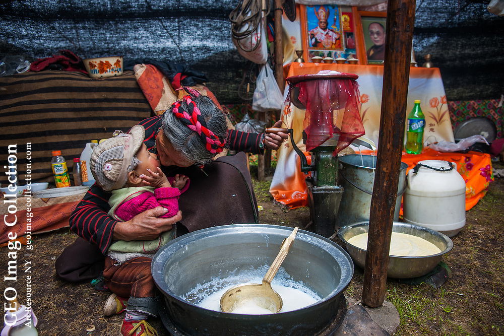 A nomad grandmother multi-tasks, making time for a hug and a kiss while churning yak butter. She and her family of seven will spend the summer here, 12 miles (20 km) from their home near Bame. Sichuan, China