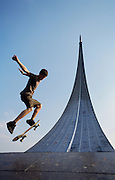Skateboarder jumping at the Momument to the Conquerors of Space, Moscow, Russia