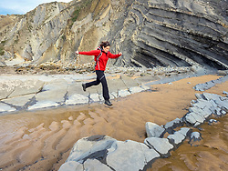 Mature Woman on a hiking tour at the cliff of Barrika