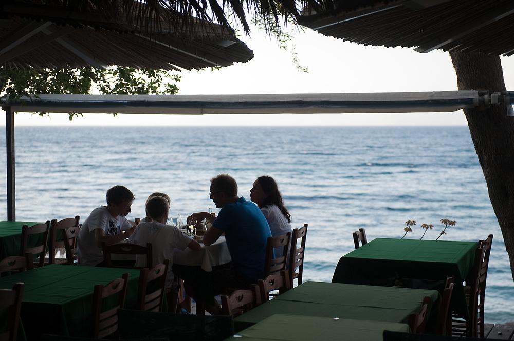 Family dining by the sea in Bastas family beach- bar and taverna in Manadendri beach, Paxoi Manadendri beach, Paxoi, Greece