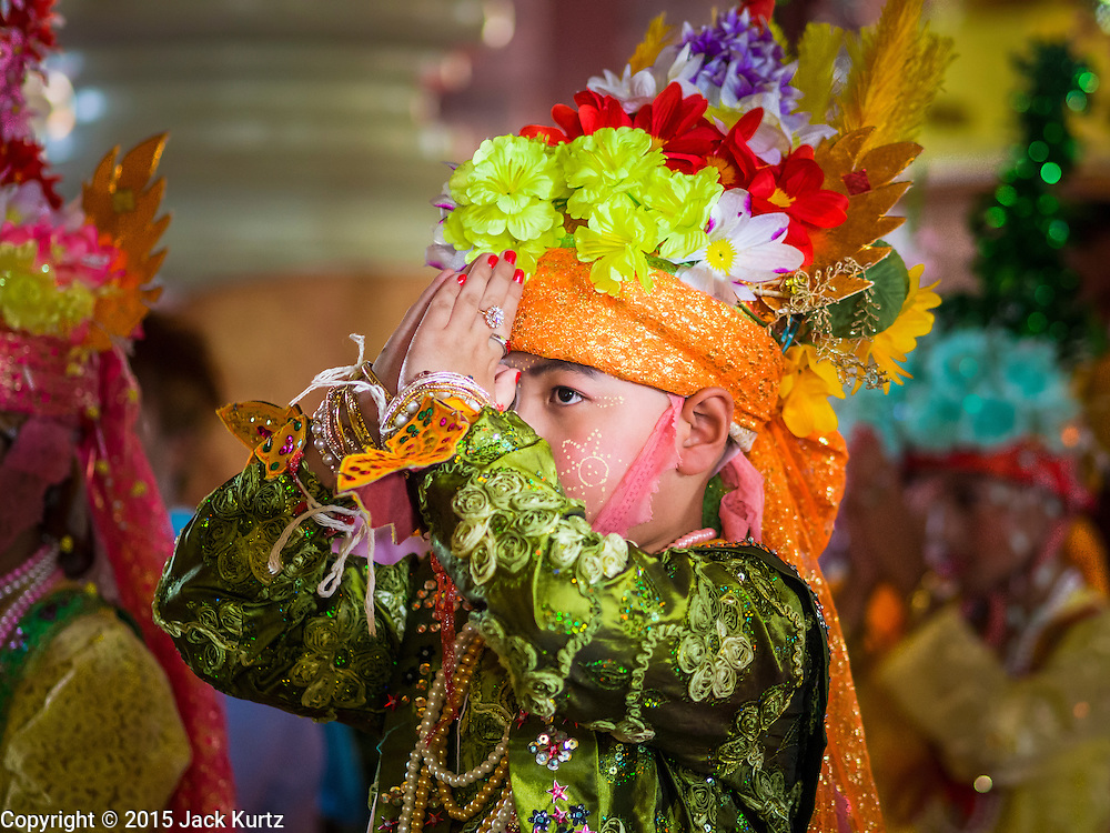 """04 APRIL 2015 - CHIANG MAI, CHIANG MAI, THAILAND: A boy being ordained as a Buddhist novice prays at Wat Phra Singh during the Poi Song Long Festival in Chiang Mai. The Poi Sang Long Festival (also called Poy Sang Long) is an ordination ceremony for Tai (also and commonly called Shan, though they prefer Tai) boys in the Shan State of Myanmar (Burma) and in Shan communities in western Thailand. Most Tai boys go into the monastery as novice monks at some point between the ages of seven and fourteen. This year seven boys were ordained at the Poi Sang Long ceremony at Wat Pa Pao in Chiang Mai. Poy Song Long is Tai (Shan) for """"Festival of the Jewel (or Crystal) Sons.      PHOTO BY JACK KURTZ"""