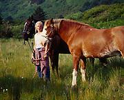 Heather Robbins with free-ranging horses belonging to Raspberry Island Lodge, Raspberry Island, Kodiak Archipelago, Alaska.