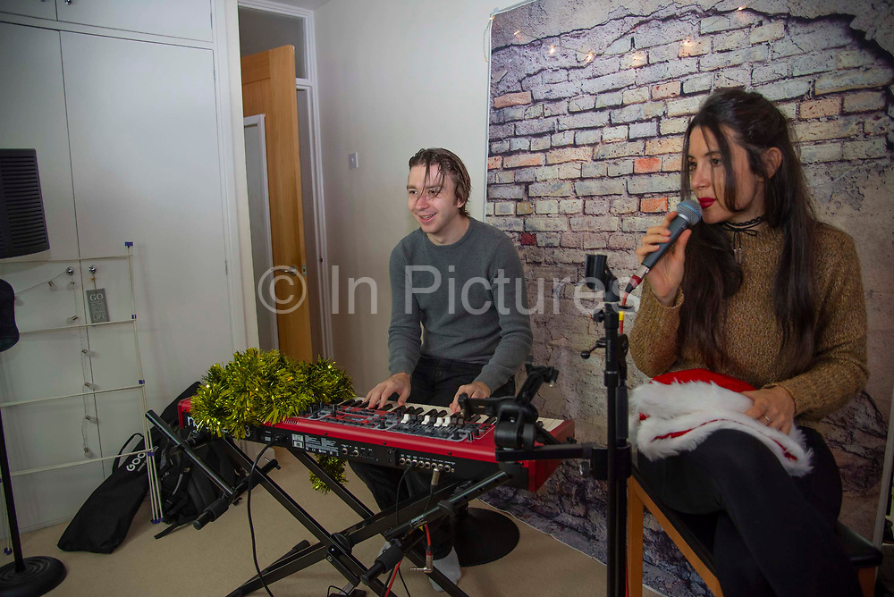 Duo Ilaria Canelli and Christopher Burgham from 2plo Music rehearse before a zoom gig on 9th December 2020 in London, United Kingdom. A recent report commisioned by music industry body UK Music, found that up to 85% of live revenue will be lost, as revenues have been close to zero since March, when live venues shut and concerts and music festivals were cancelled. 2plo lost all gig work over night and have only recently began performing again via zoom, with the help of a entertainment website called Lockdown Presents.