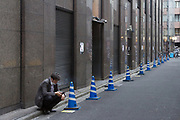 A Japanese office worker or sallaryman smokes in a street in Shinjuku, Tokyo, Japan. Friday May 22nd 2020