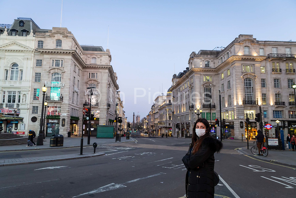 A woman wearing a face mask stands in an almost deserted Picadilly Circus in London on March 27th, 2020. The centre of London is extremely quiet with almost every business closed and very few people about because of the Governments lockdown measures due to the Coronavirus crisis.