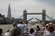 Tourists take a sightseeing tour cruise boat down the River Thames taking in some of the famous landmarks, skylines and iconic buildings in the capital like here passing Tower Bridge, operated by City Cruises in London, England, United Kingdom.