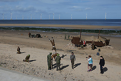 © Licensed to London News Pictures. 26/04/2016. Redcar, UK. As part of the build up to the 2018 Festival of Thrift 80 volunteers help artist and film-maker Richard DeDomenici (2ndR) to make a 'Redux' version of the five minute Dunkirk scene from the 2007 Oscar winning film Atonement on Redcar beach. The Festival of Thrift, 19th – 25th August 2018, is a week-long programme of temporary art installations in locations across the Tees Valley landscape. Photo credit: Nigel Roddis/LNP
