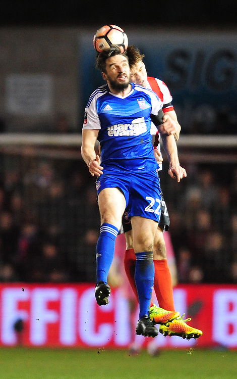 Ipswich Town's Jonathan Douglas vies for possession with Lincoln City's Sean Raggett<br /> <br /> Photographer Chris Vaughan/CameraSport<br /> <br /> Emirates FA Cup Third Round Replay - Lincoln City v Ipswich Town - Tuesday 17th January 2017 - Sincil Bank - Lincoln<br />  <br /> World Copyright © 2017 CameraSport. All rights reserved. 43 Linden Ave. Countesthorpe. Leicester. England. LE8 5PG - Tel: +44 (0) 116 277 4147 - admin@camerasport.com - www.camerasport.com