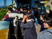 PAJU, GYEONGGI, SOUTH KOREA: South Korean tourists look into North Korea at Dora Observatory, on the edge of the DMZ. Tourism to the Korean DeMilitarized Zone (DMZ) has increased as the pace of talks between South Korea, North Korea and the United States has increased. Some tours are sold out days in advance.      PHOTO BY JACK KURTZ