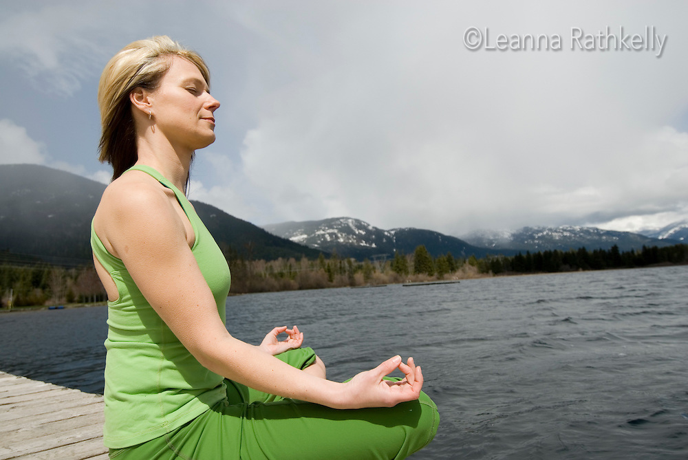 A woman meditates on a dock by Alta Lake in Whistler, BC Canada
