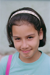 Portrait of young girl wearing hair band; smiling,