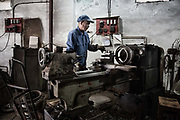 A machinist working at a small shop in Xingxing village on the outskirts of Shanghai,  China on 14 August 2015.  As Chinas sputtering economy has beginning to affect employment, many migrants who used to live in the village to work on Shanghais numerous construction sites and factories are beginning to thin out.