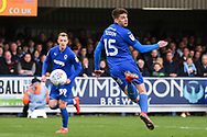 AFC Wimbledon Defender Steve Seddon (15) takes a shot on goal during the EFL Sky Bet League 1 match between AFC Wimbledon and Wycombe Wanderers at the Cherry Red Records Stadium, Kingston, England on 27 April 2019.