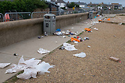 The morning after Saturday night crowds of young peoples nightlife beach parties, their litter and rubbish from the night before is trewn across the coastal paths and shingle along the sea wall, on 19th July 2020, in Whitstable, Kent, England.  A group of local volunteers and council cleaner will soon arrive for the regular morning clean-up that has got worse, they say, during the Coronavirus pandemic lockdown and now, the slow easing of health guidelines.