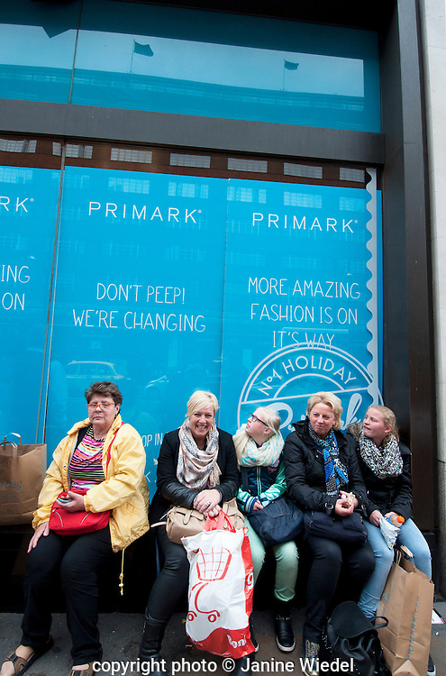 Shoppers sitting outside Primark in Oxford Street tired from bargain shopping