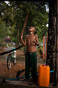 A child plays with the rain, Tanintharyi Region, Burma.<br />