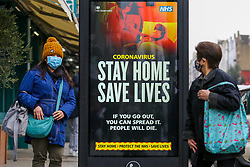 © Licensed to London News Pictures. 10/01/2021. London, UK. Women wearing protective face coverings look at the Government's 'Stay Home, Save Lives' Covid-19 publicity campaign poster in north London, as the number of cases of the mutated variant of the SARS-Cov-2 virus continues to spread around the country. The message in the advertising campaign poster asks people to act like they have Covid. Almost 60,000 new cases of coronavirus were reported in the UK on Saturday 9 January 2021 and the number of deaths after a positive test passed 80,000, since the pandemic began. Photo credit: Dinendra Haria/LNP