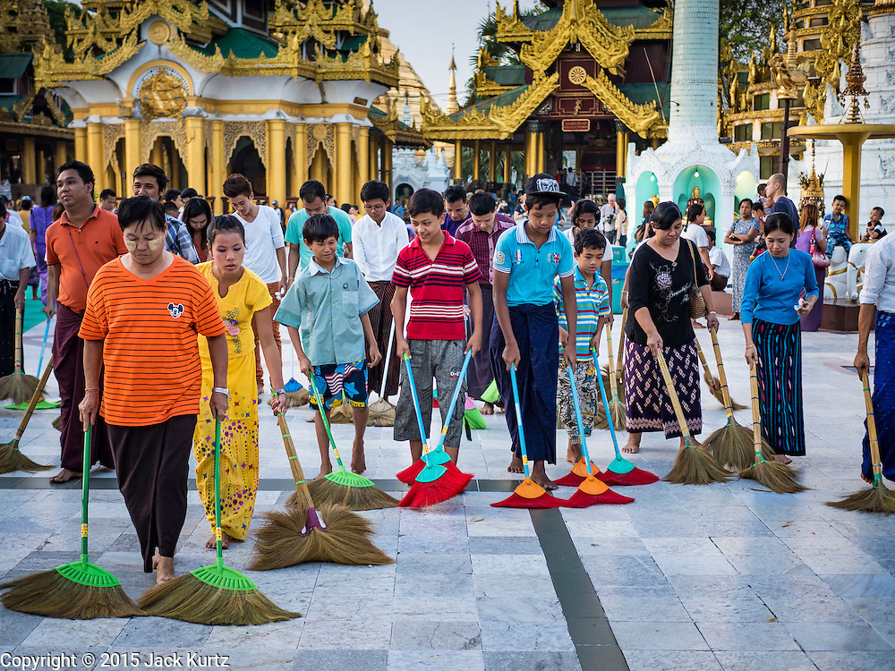 31 OCTOBER 2015 - YANGON, MYANMAR: Volunteers clean the plaza around Shwedagon Pagoda to make merit. Shwedagon Pagoda is officially known as Shwedagon Zedi Daw and is also called the Great Dagon Pagoda or the Golden Pagoda. It is a 99 metres (325ft) tall pagoda and stupa located in Yangon, Burma. The pagoda lies to the west of on Singuttara Hill, and dominates the skyline of the city. It is the most sacred Buddhist pagoda in Myanmar and contains relics of four past Buddhas: the staff of Kakusandha, the water filter of Koṇāgamana, a piece of the robe of Kassapa and eight strands of hair from Gautama, the historical Buddha. The pagoda was built between the 6th and 10th centuries by the Mon people, who used to dominate the area around what is now Yangon (Rangoon). The pagoda has been renovated numerous times through the centuries. Millions of Burmese and tens of thousands of tourists visit the pagoda every year, which is the most visited site in Yangon.      PHOTO BY JACK KURTZ