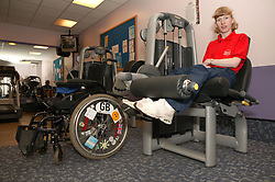 Access to services, Disabled woman in the gym; using Leg Extension,