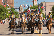Cowboys soldiers dressed in period costume riding in the Cheyenne Frontier Days parade past the state capital building July 23, 2015 in Cheyenne, Wyoming. Frontier Days celebrates the cowboy traditions of the west with a rodeo, parade and fair.