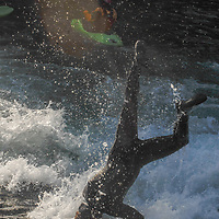 A river surfer does a head stand on a wave in the Kananaskis River near Calgary, Alberta, Canada.