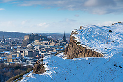 View of Salisbury Crags covered in snow in winter in Holyrood Park with Edinburgh Castle to rear, Edinburgh, Scotland, UK