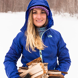 A woman carrying fire wood while winter camping in New Hampshire's White Mountains. Randolph Community Forest.