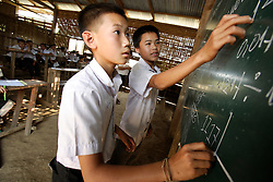 Sorkhai, 11 yrs old writes on the blackboard to complete complex mathematical tasks.  Vang Mak primary school, Vieng thong district, Bolikhamxai Province, Lao PDR