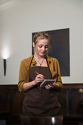 Young waitress in apron taking order at restaurant