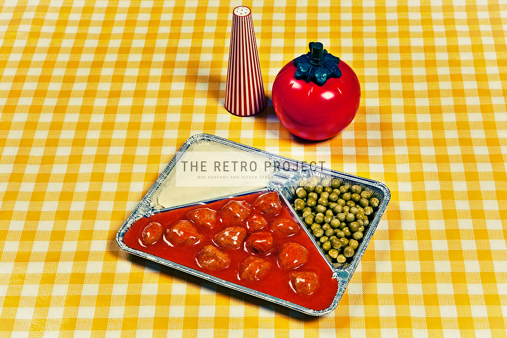 TV Dinner aluminium tray meal with meatballs, peas and potato mash on Chequered orange vinyl table cloth background with pepper pot and tomato sauce plastic bottle