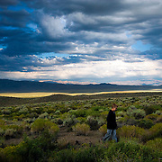 A young teenager makes his way through a valley as a late afternoon thunderstorm moves over the Owens Valley near Mammoth Lakes,  CA and Benton Crossing in the eastern Sierra.