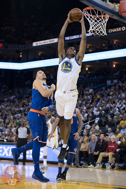 January 23, 2018; Oakland, CA, USA; Golden State Warriors forward Kevon Looney (5) dunks the basketball against New York Knicks center Willy Hernangomez (14) during the third quarter at Oracle Arena. The Warriors defeated the Knicks 123-112.